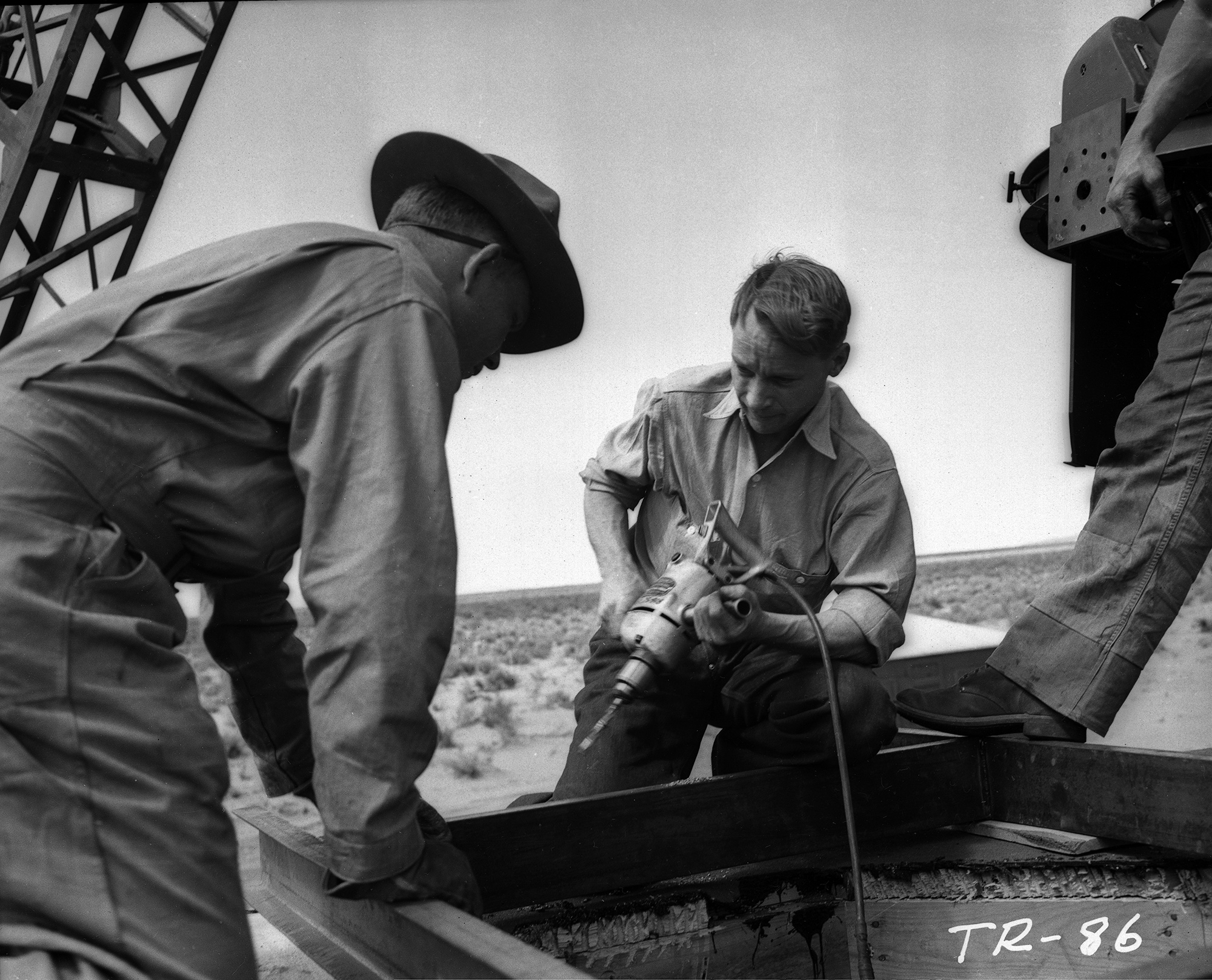 Drilling channel on top of 10,000 yard N shelter. B.C. Benjamin and Berlyn Brixner (Center)
