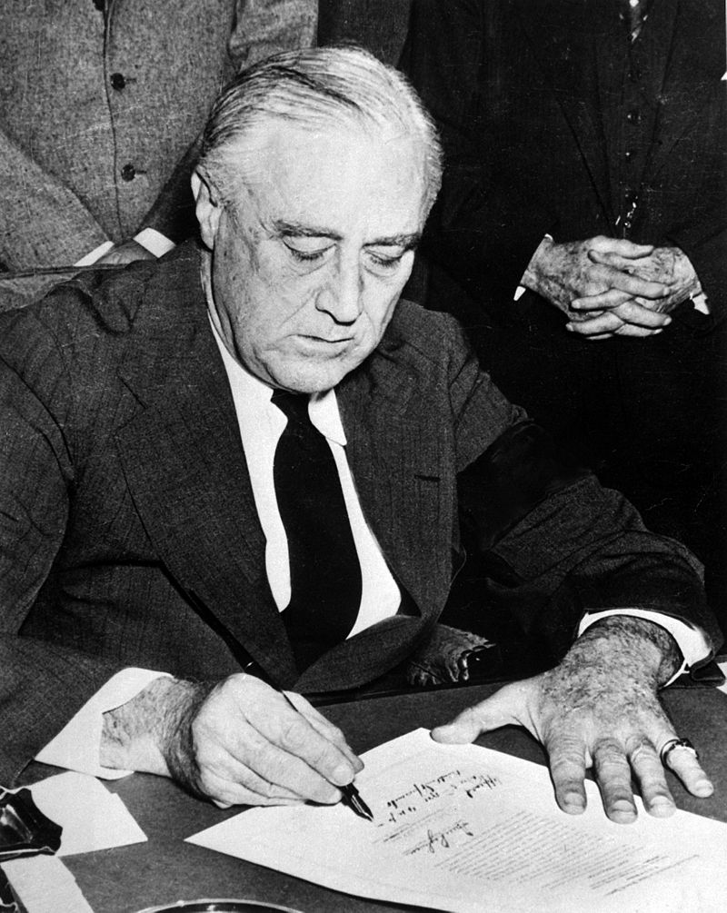 President Roosevelt, wearing a black armband, signs the declaration of war against Japan on December 8, 1941