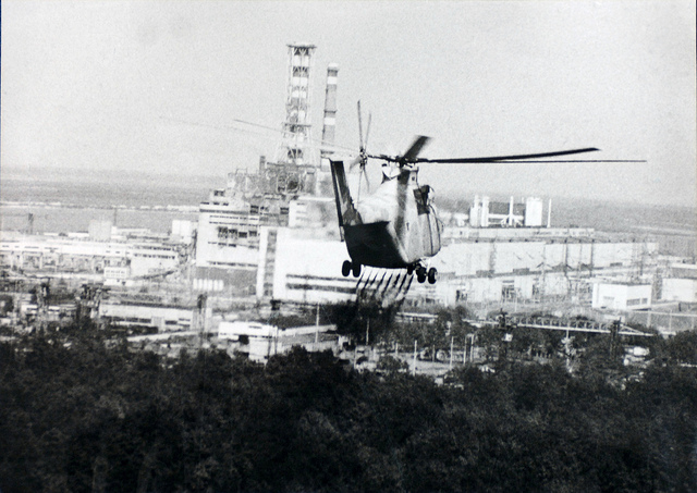 A helicopter moves in to help experts check the damage to the Chernobyl reactor in 1986. (Chernobyl, Ukraine, 1986). Photo Credit: USFCRFC from IAEA Imagebank Flickr