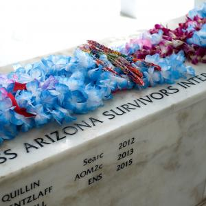 Flowers honoring the survivors interred with their shipmates