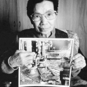 """Matsushige's wife holding a photo of herself. Original caption: """"Matsushige's wife, wearing air raid helmet, attempts to clear some of the rubble in their barbershop home. About 2pm, 2.7 kilometers from the hypocenter."""""""