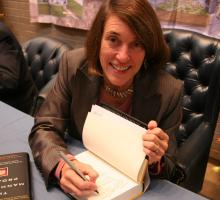 AHF President Cindy Kelly signing copies of The Manhattan Project anthology
