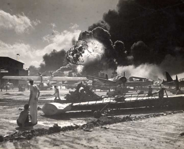 Sailors stand amid wrecked planes at the Ford Island seaplane base, watching as USS Shaw explodes in the center background