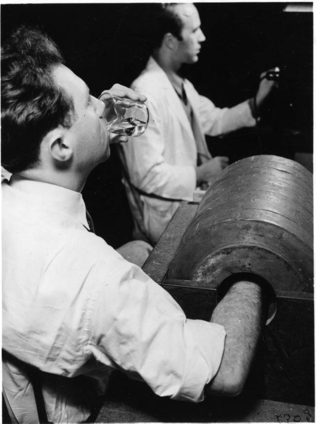 Joseph G. Hamilton drinking radiosodium for a demonstration, alongside Robert Marshak