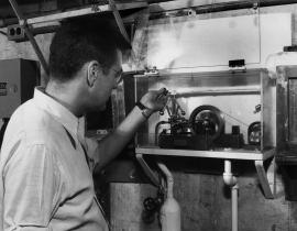 Logan Emlett examines the toy steam engine and bulb apparatus at the Graphite Reactor in 1948. Photo courtesy of DOE.