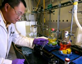 Jun Yang inspects a sample in the hood in the small molecule synthesis lab. Photo courtesy of DOE.
