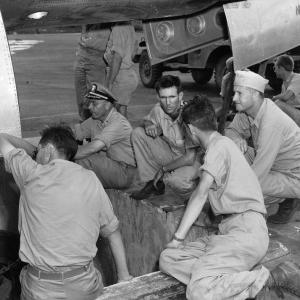 Manhattan Project scientists and military personnel gather around the bomb pit, ready to watch the Little Boy bomb being loaded into the Enola Gay