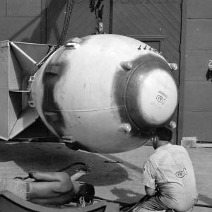 "The sealant has been applied. Note the signatures on the tail assembly and the ""bomb"" on the worker's shirt"