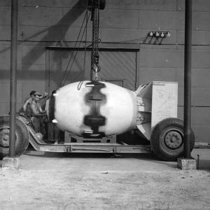 Fat Man is lowered on to a transport dolly for the trip to the airfield. Note the signatures on the tail assembly