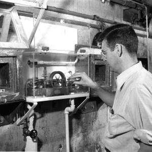 Logan Emlet runs atomic powered apparatus that lights a light bulb, 9-3-1948