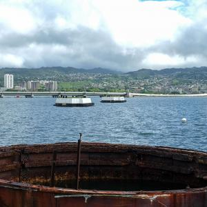 A section of the USS Arizona above the water, with Honolulu in the background