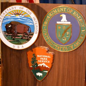 DOE, DOI, and NPS logos on the podium at the signing ceremony