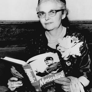 Laura Fermi, later in life, holding a copy of her book Mussolini