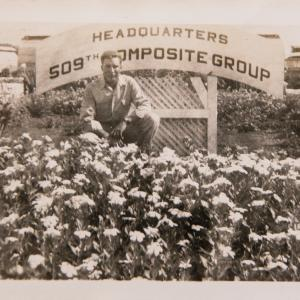 Mack Newsom in front of the 509th headquarters sign on Tinian