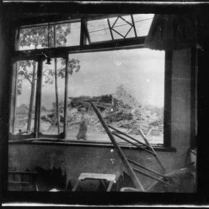 "Original caption: ""A four-story wooden fire station reduced to rubble outside barber shop window. About 2pm, 2.7 kilometers from hypocenter."""