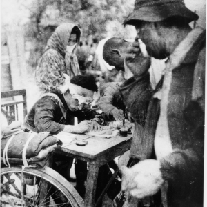 "Original Caption: ""An injured policeman writes relief certificates for rice rations to A-bomb survivors. Taken at tram stop near the Miyuki Bridge about 5pm, 2.4 kilometers from the hypocenter."""