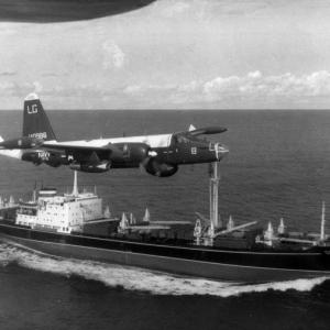 A U.S. Navy Lockheed P-2 Neptune flies over a Soviet freighter, 1962