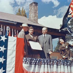 """J. Robert Oppenheimer, General Leslie Groves, and University of California President Robert Sproul present the Army-Navy """"E"""" Award to Los Alamos National Laboratory in October 1945."""
