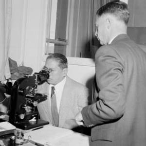 The Chairman of the Philippines National Development Board, Dr Paulino J Garcia, looks through an electro microscope while Professor E. W. Titterton, looks on (1959)