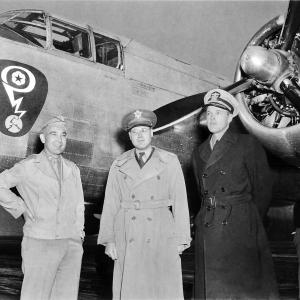 Colonel Franklin Matthias, Colonel Kenneth Nichols, and an unknown man in front of a plane with the Manhattan Project insignia