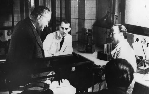 Lew Kowarski conversing with Frederic Joliot-Curie and Hans Halban in a laboratory. Photo courtesy of  J. Gueron, courtesy of AIP Emilio Segrè Visual Archives.